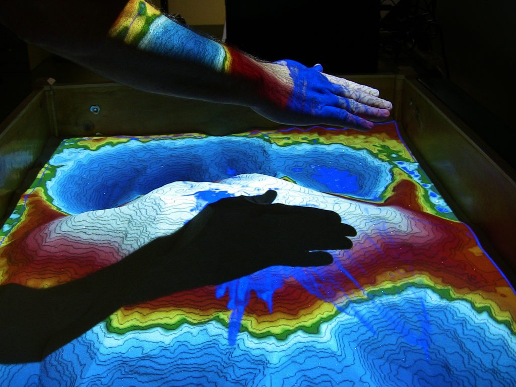 hand over topographical map demonstrating projection